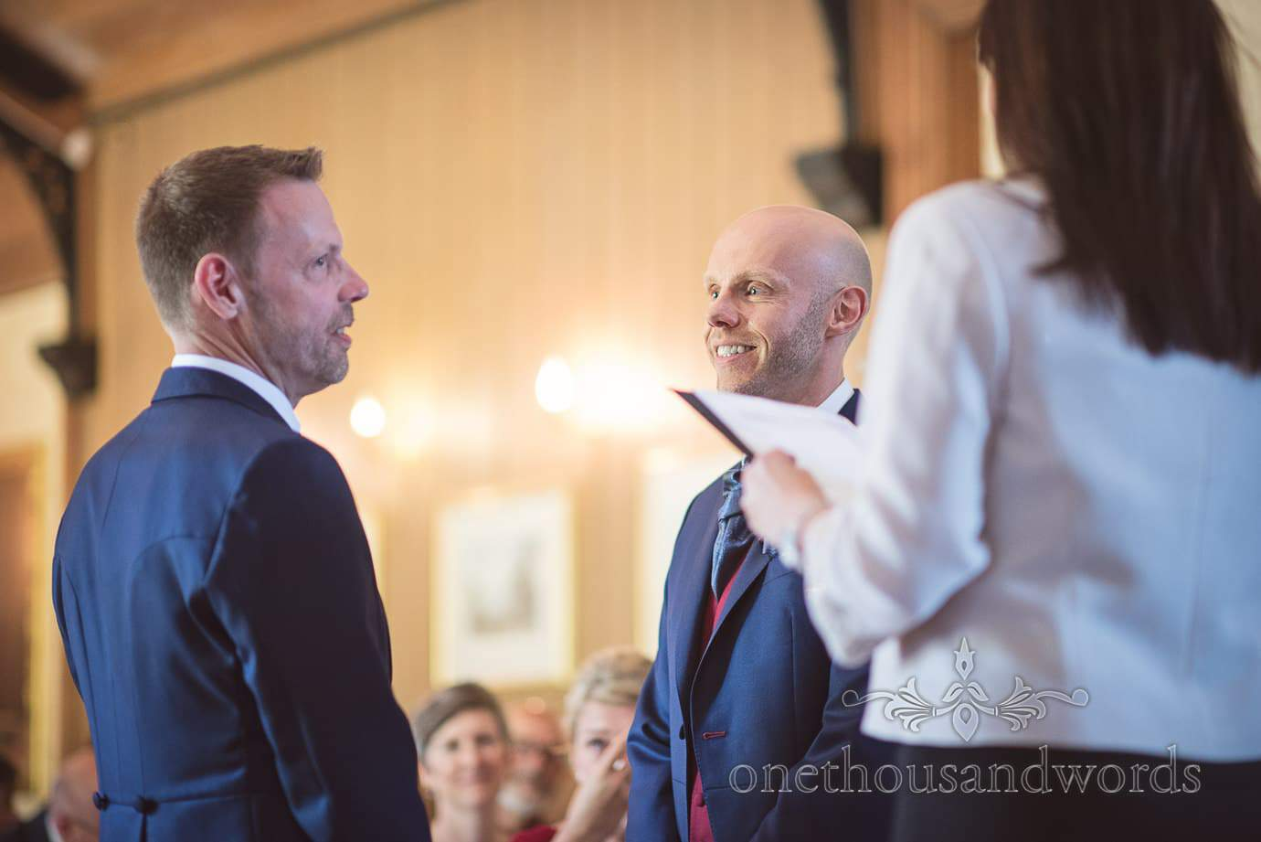 Groom in blue suit smiles at partner during gay wedding ceremony vows