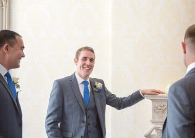 Groom in grey wedding suit with blue tie and handkerchief rests on fireplace