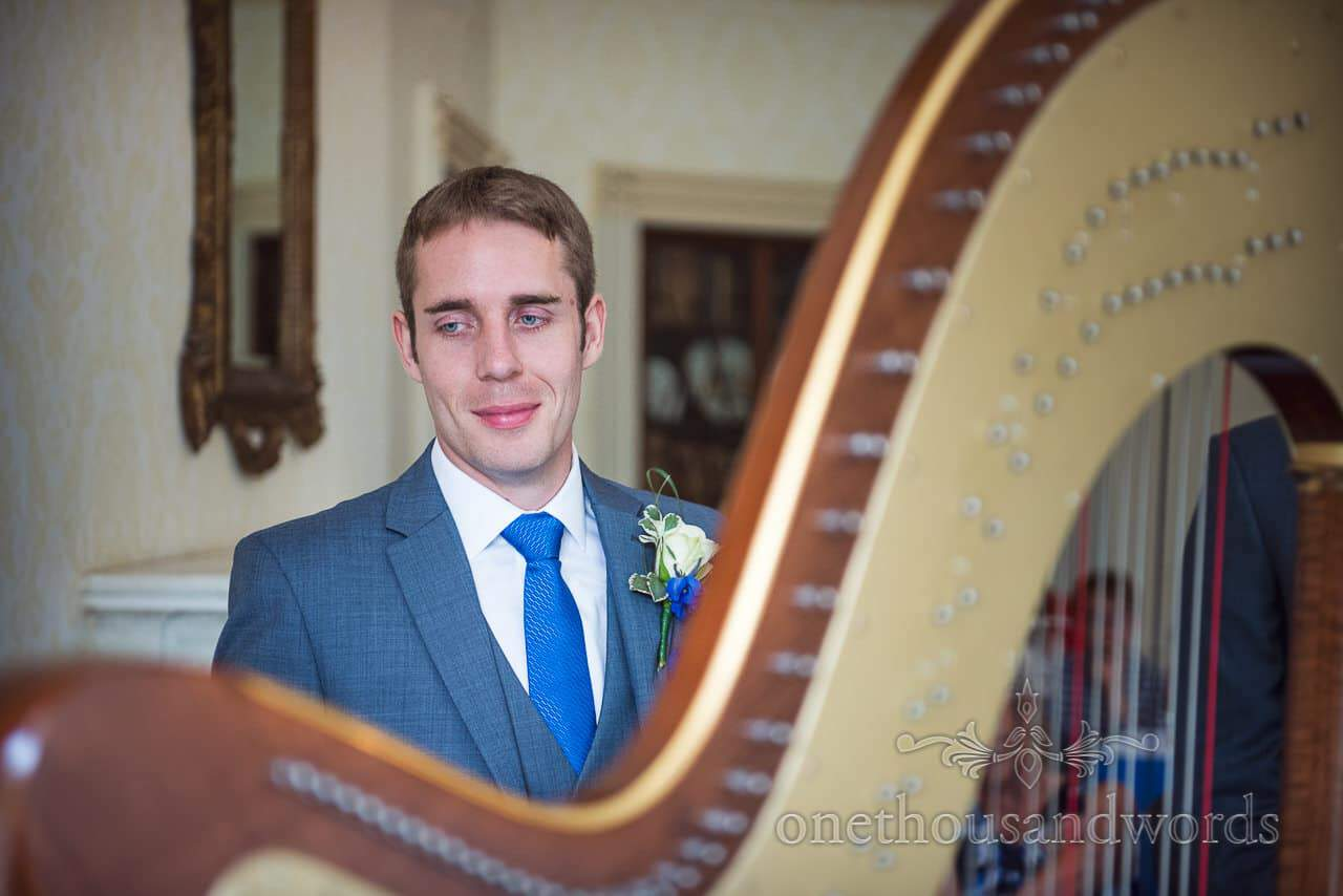 Groom in grey wedding suit with blue tie watches wedding harpist at Upton House
