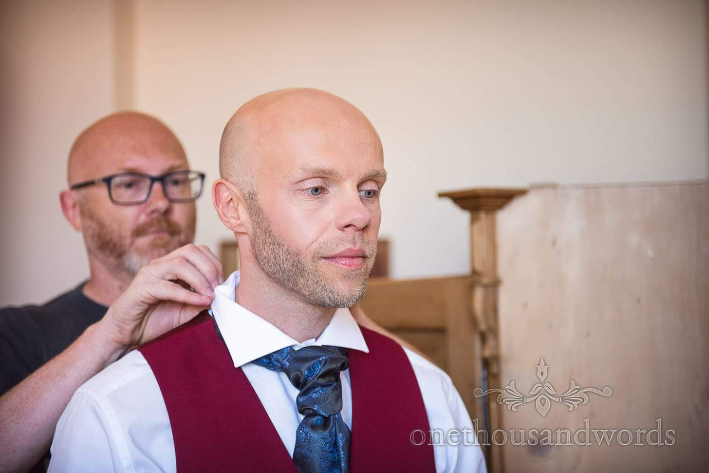Groom in red waistcoat has cravat tied on wedding morning in Swanage, Dorset