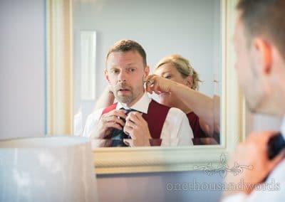 Groom is helped into wedding cravat in mirror on Swanage wedding morning