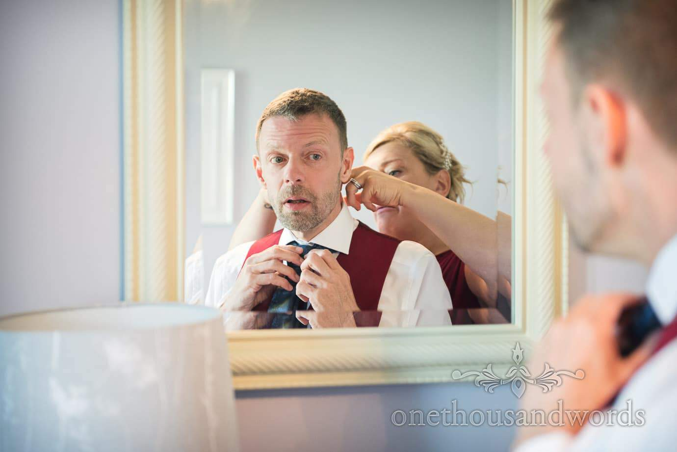 Groom is helped into wedding cravat in mirror on Swanage wedding morning