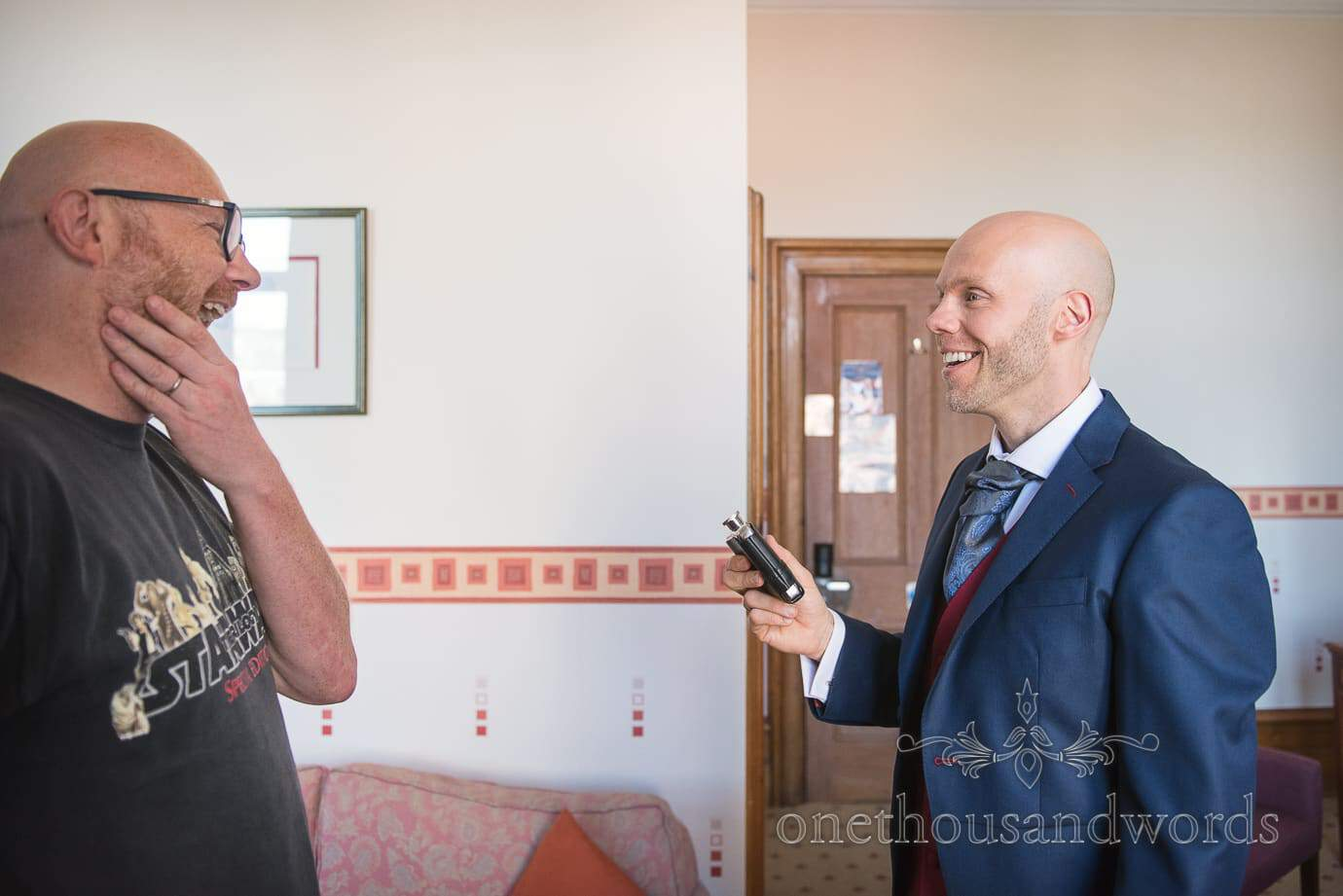 Groom laughs with brother on Wedding morning preparations in Swanage