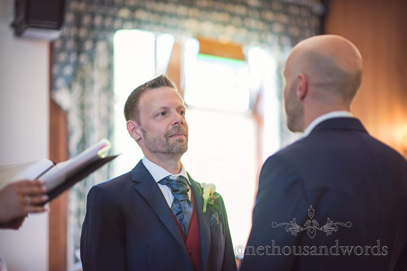 Groom looks affectionately into partners eyes during gay wedding ceremony in Dorset