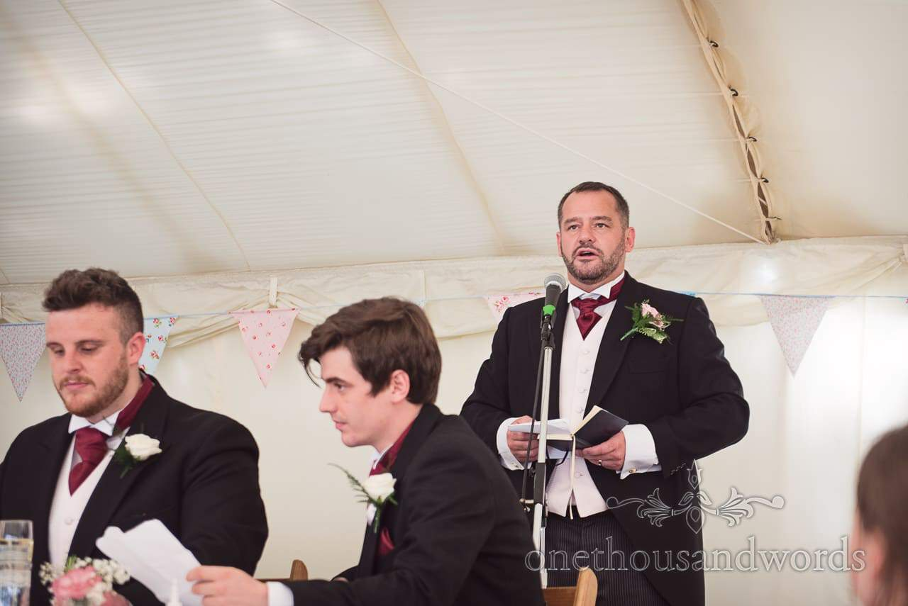 Groom reads grooms speech in black wedding tails with red cravat in wedding marquee