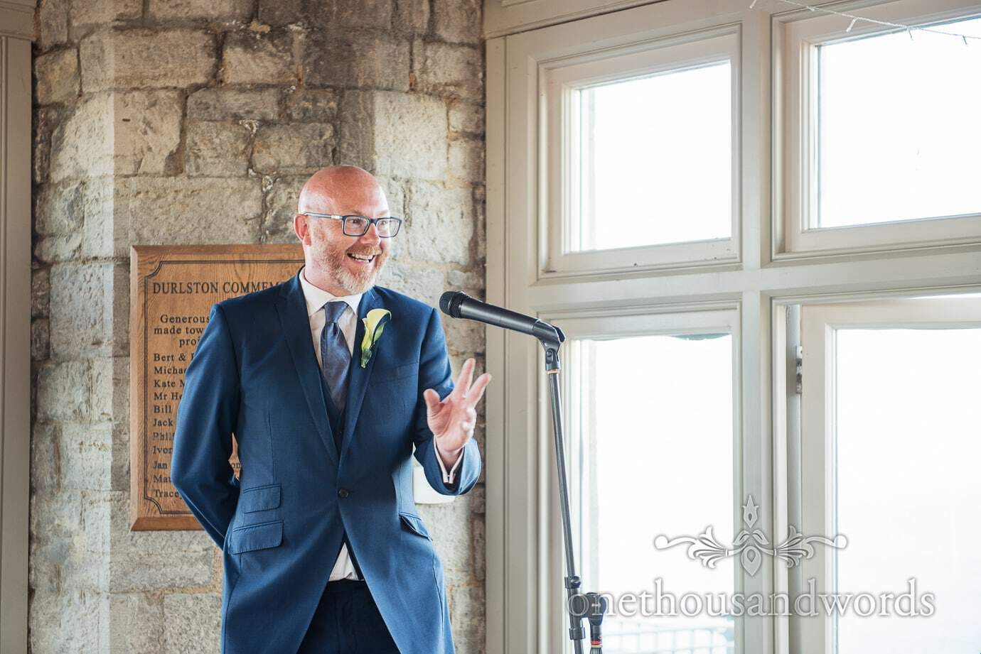 Groom's brother in blue wedding suit give animated wedding speech at Durlston Castle