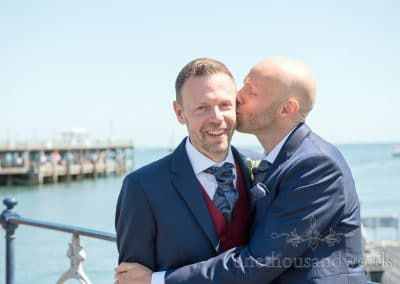 Groom's in blue wedding suits kiss by the sea on Swanage Victorian Pier