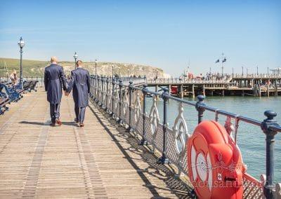 Groom's in blue wedding suits walk hand in hand along Swanage Victorian pier