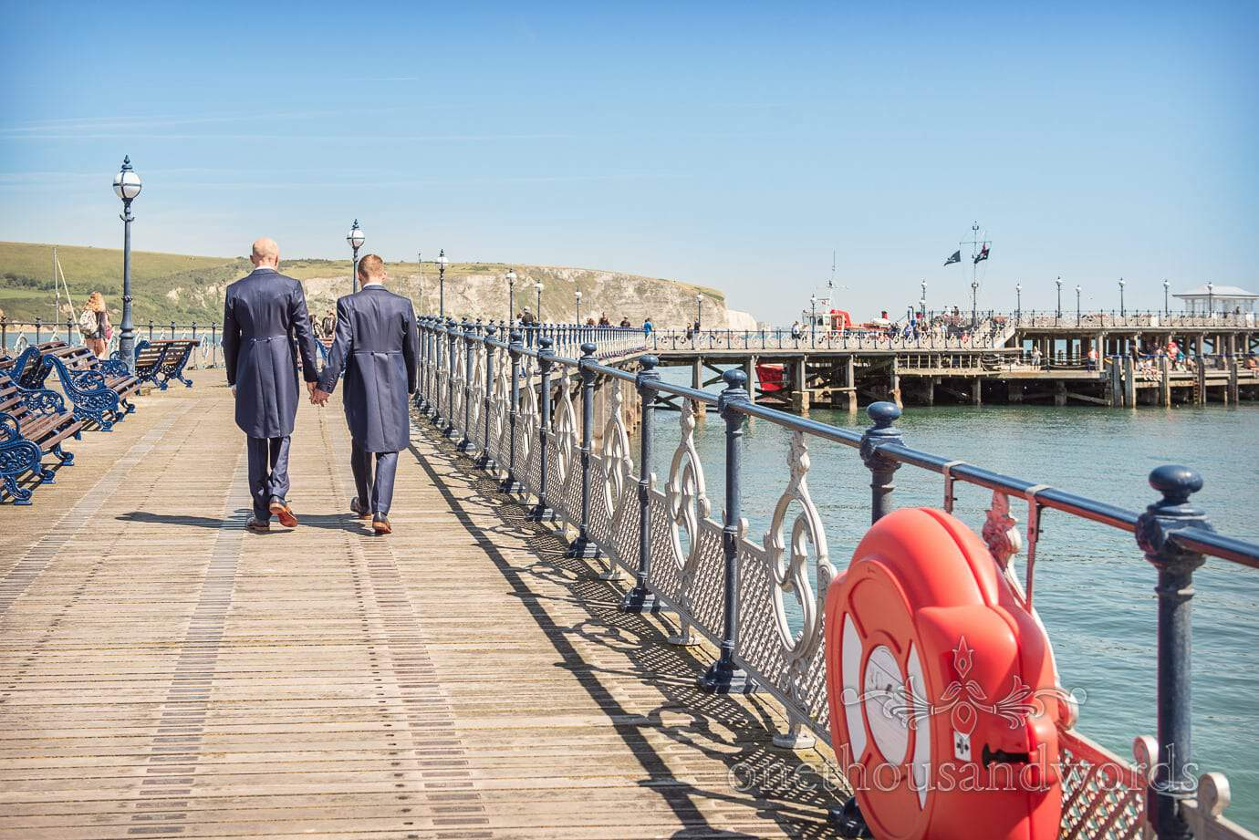 Groom's in blue wedding suits walk hand in hand along Swanage Victorian pier