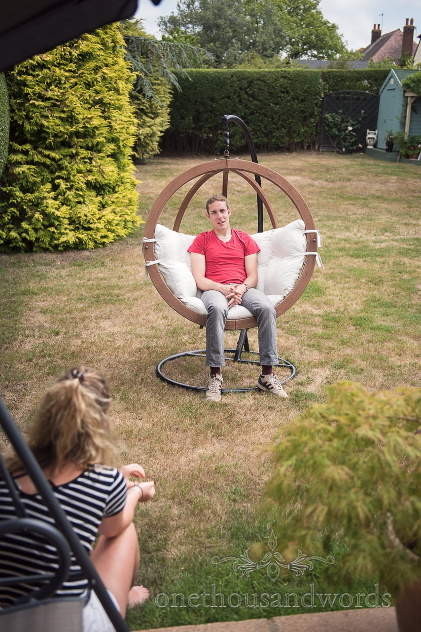 groom sits in circular hanging chair in garden on wedding morning in Poole