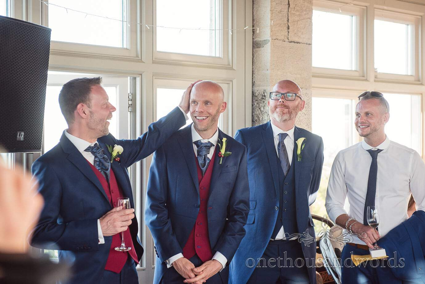 Groom strokes other grooms head during speeches at same sex wedding in Swanage, Dorset