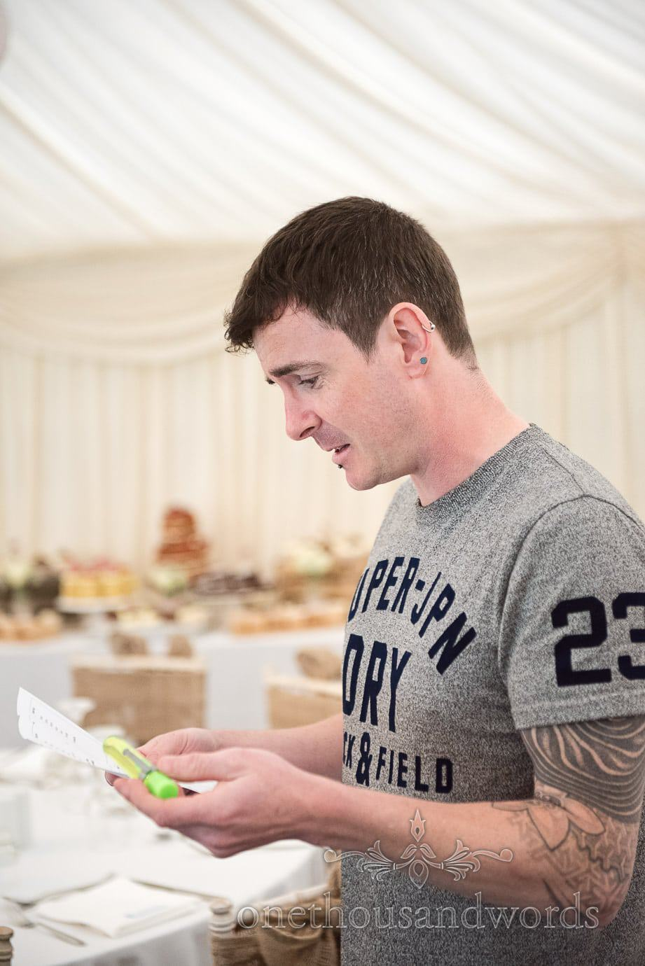 Groom with tattoo sleeve looks at to do list on in The Old Vicarage wedding marquee