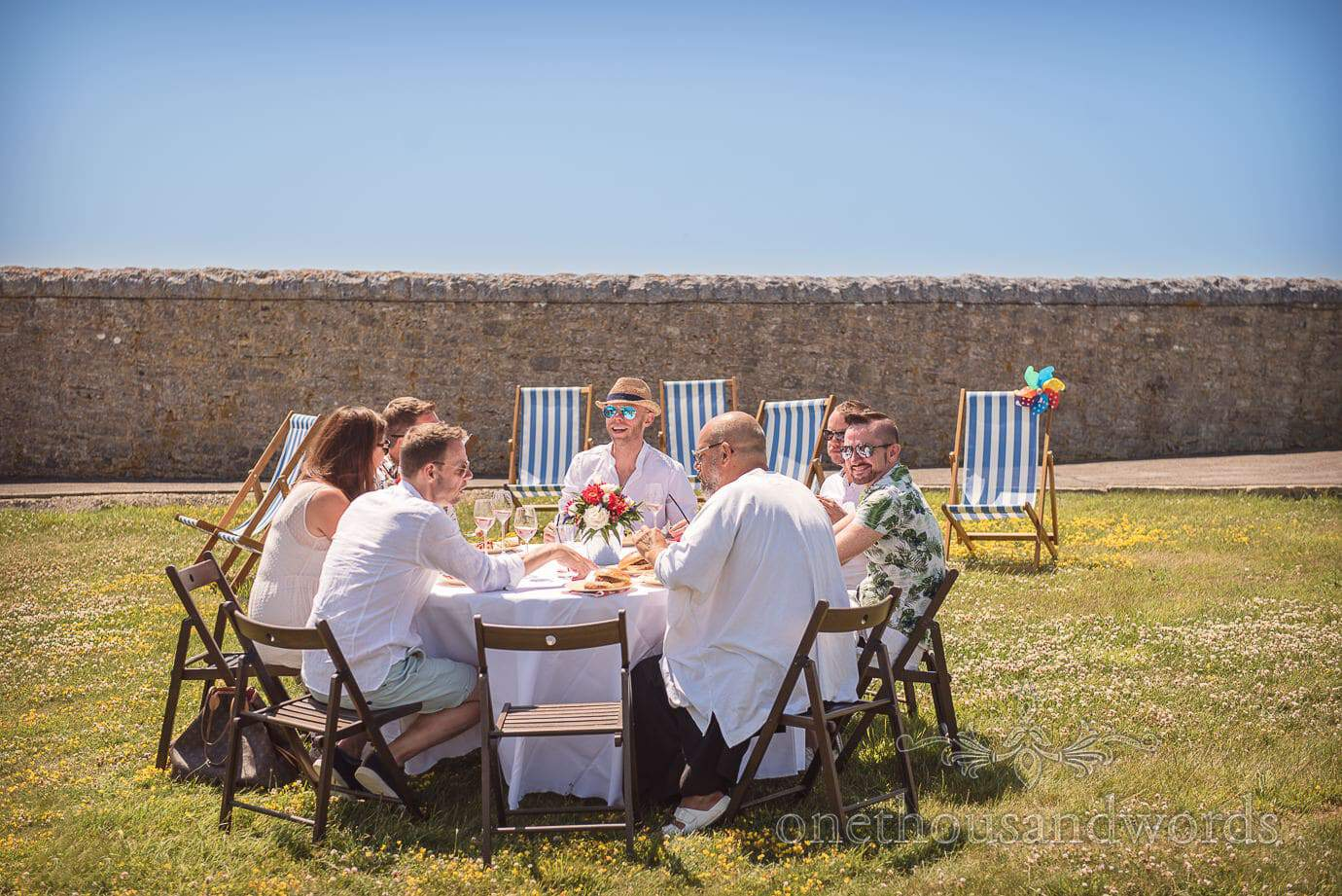 Grooms host post wedding meal at Durlston Lighthouse by Swanage wedding photographers