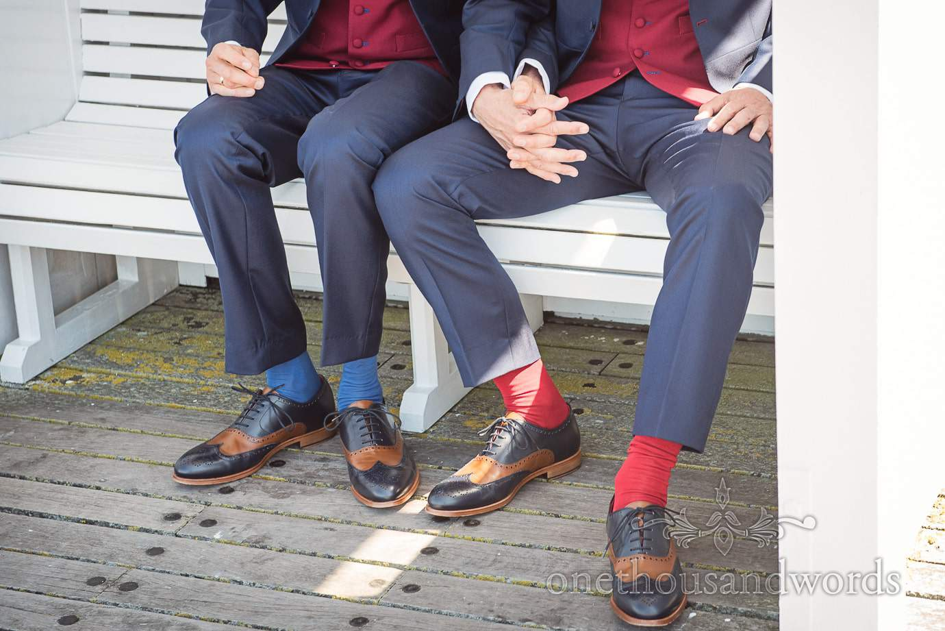 Grooms in blue wedding suits with blue and red socks and blue and tan wedding shoes