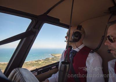 Grooms look over Dorset coastline during wedding helicopter ride