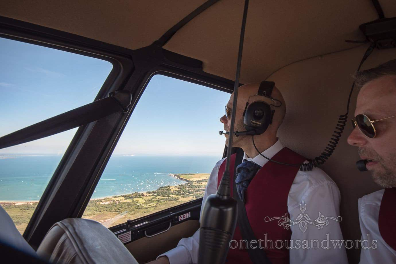 Grooms look over Dorset coastline during wedding helicopter ride