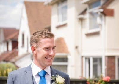 Grooms man in grey suit enjoys the sunshine outside family home on wedding morning