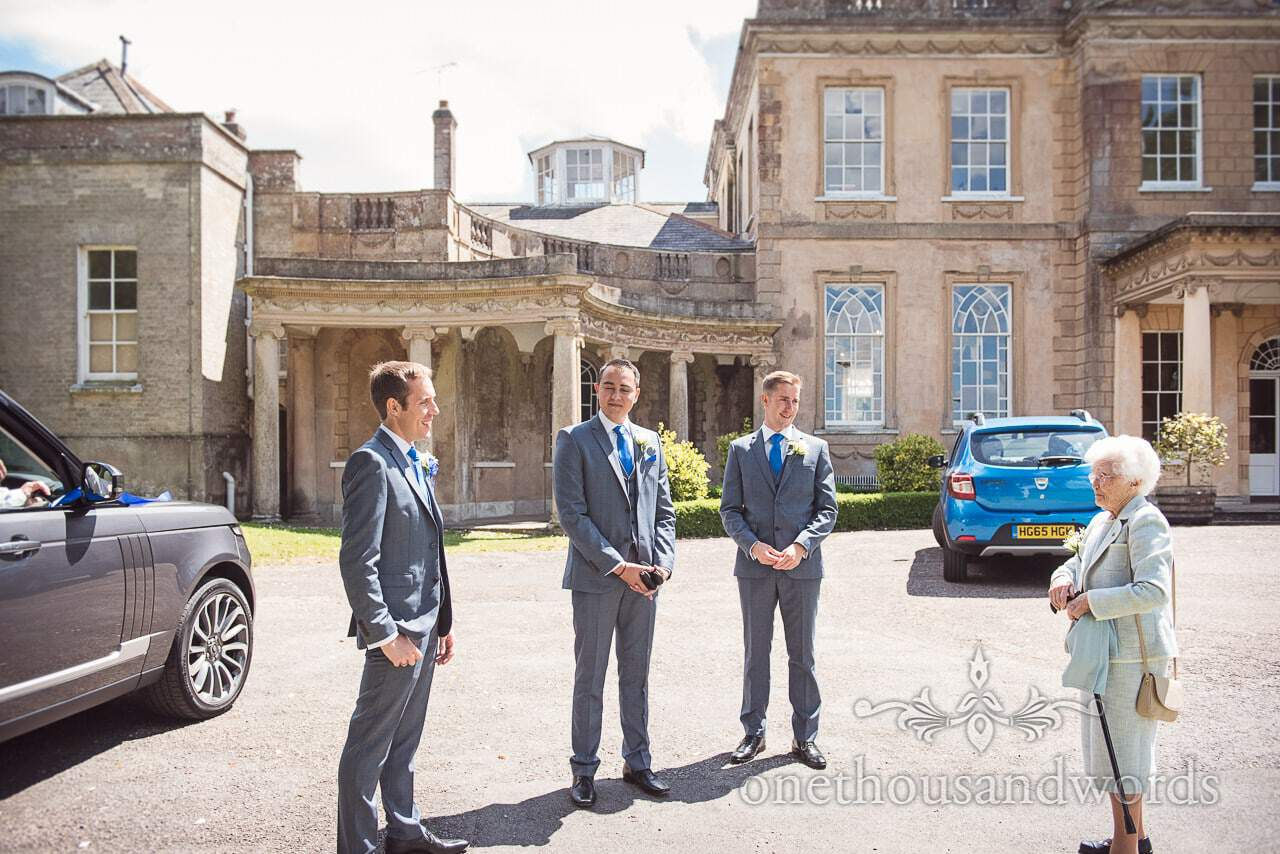 Grooms men in grey suits and blue ties greet granny at Upton House wedding