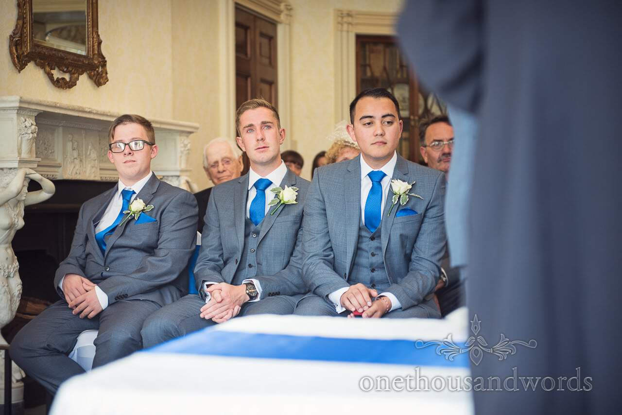 Grooms men in grey suits with blue ties cry during wedding ceremony at Upton House