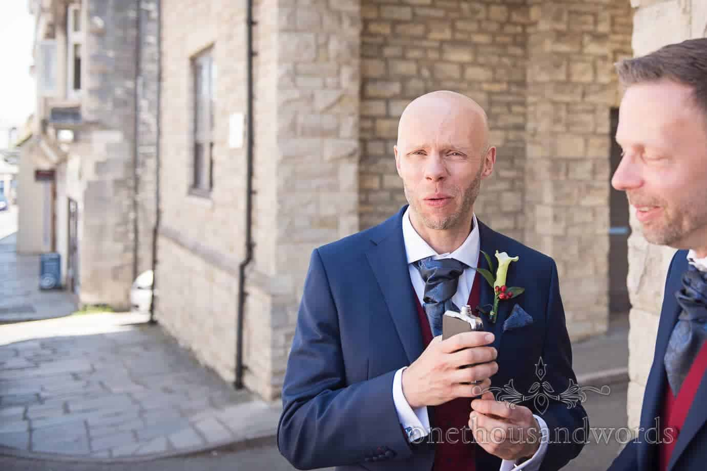 Grooms reaction to hip flask whiskey on wedding morning in Swanage, Dorset