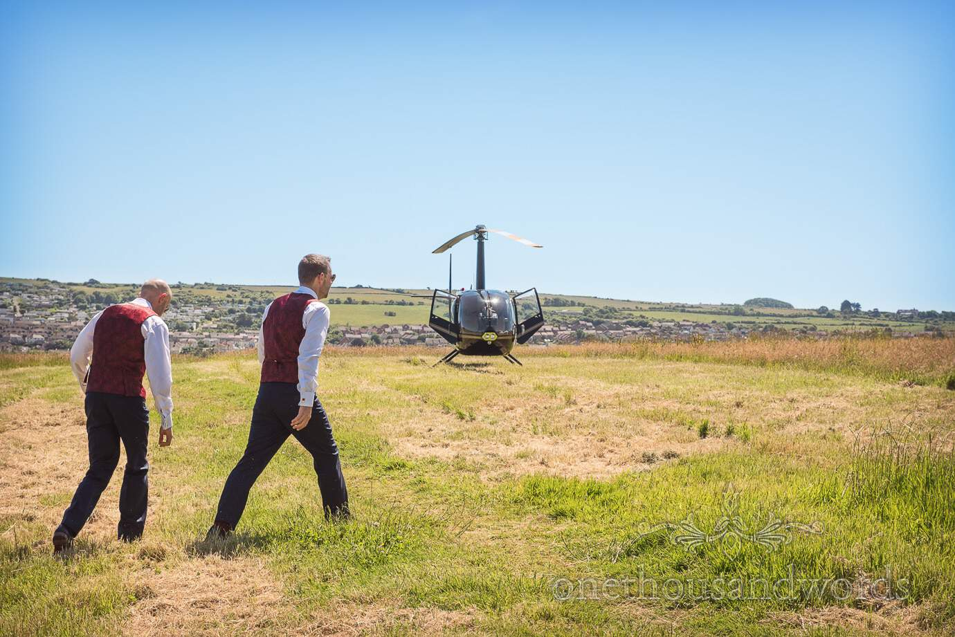 Grooms walk to wedding helicopter in Dorset countryside field