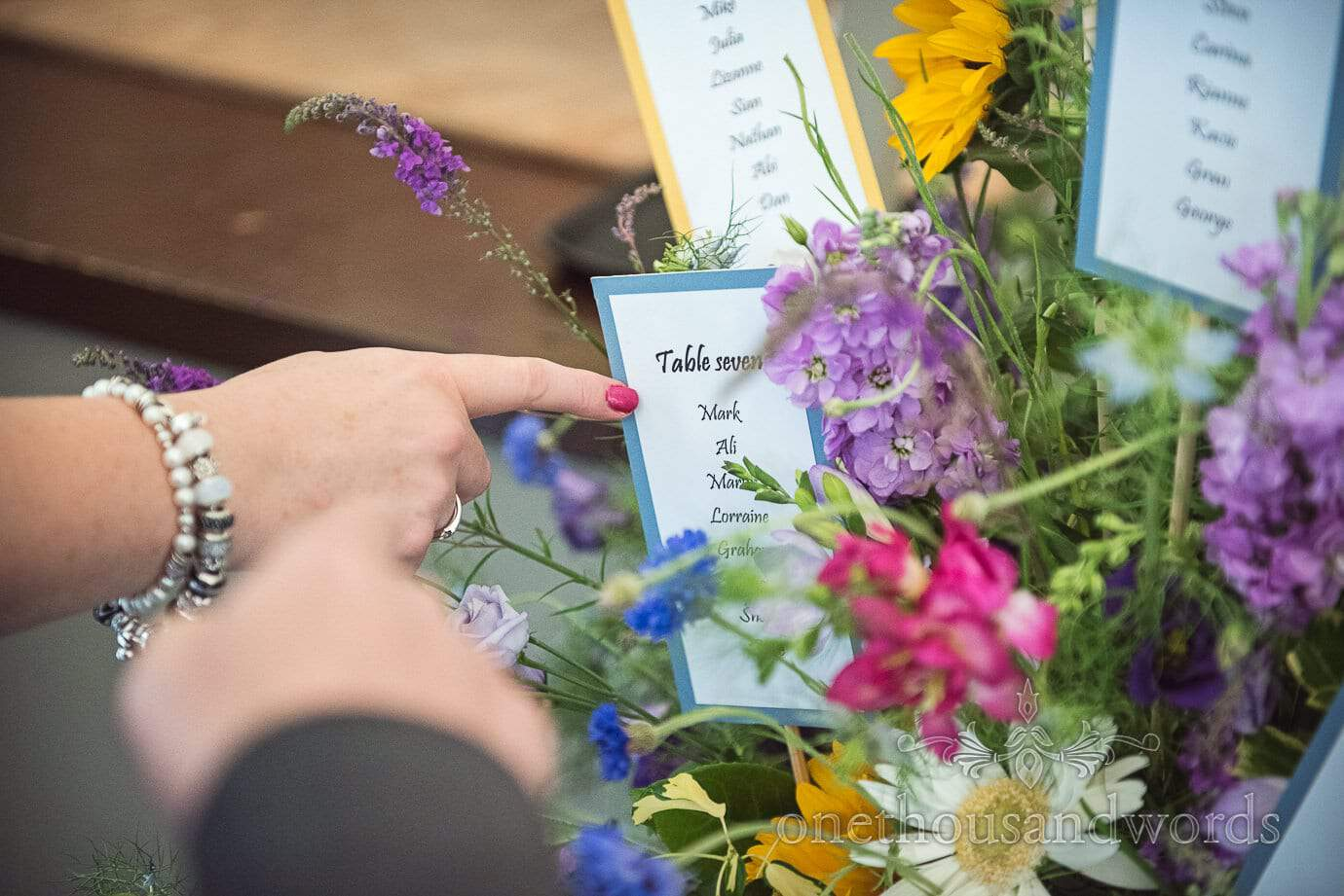 Guests point at floral table plan The Old Vicarage Wedding venue in New Forest
