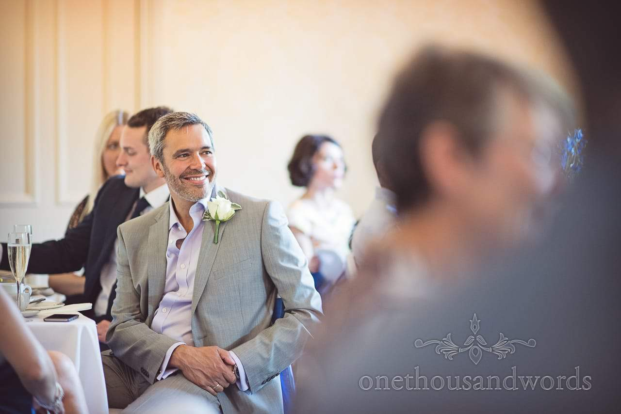 Handsome wedding guest in grey suit with white button hole smiles during speeches