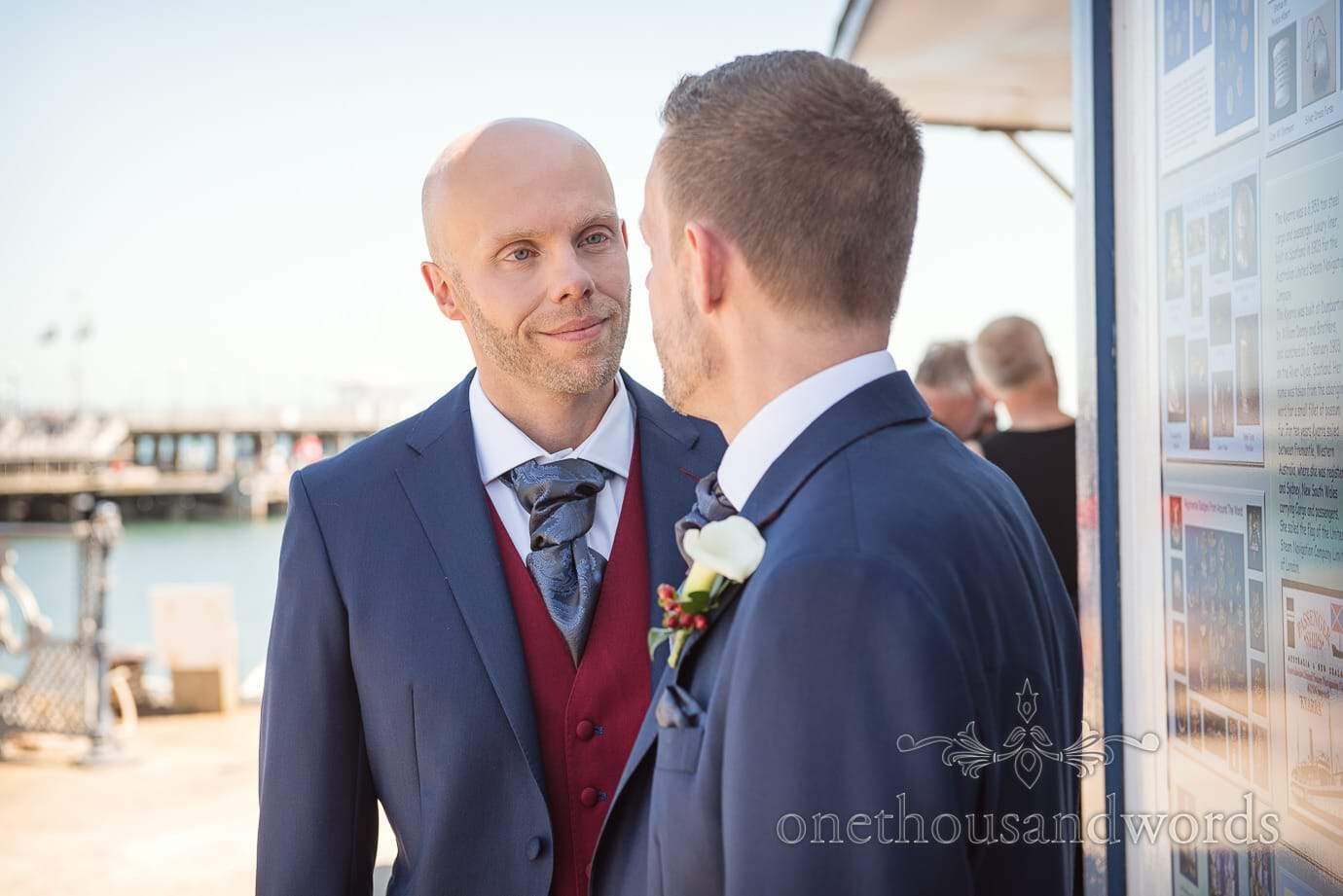 Happy same sex grooms in red and blue wedding suits on Swanage pier in Dorset