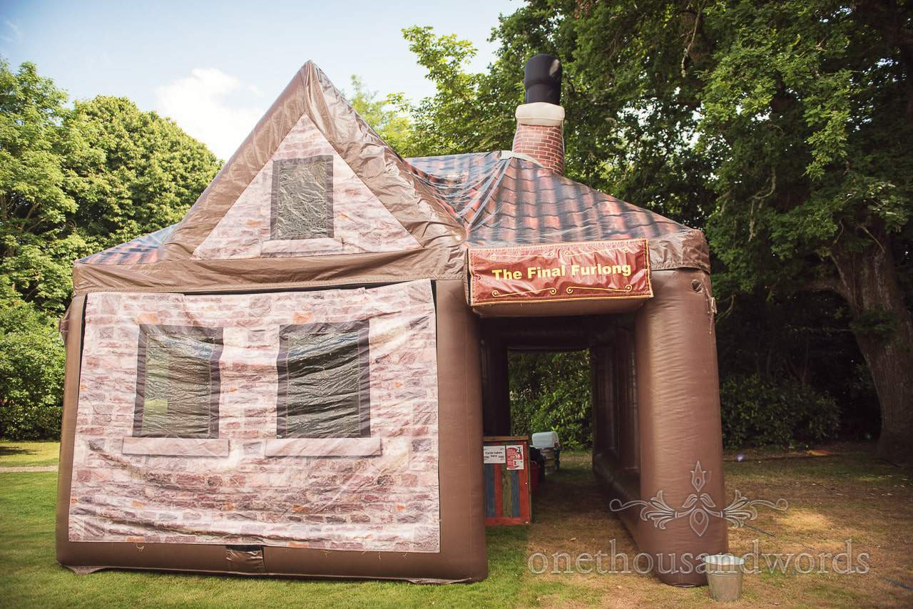 Inflatable pub with tiled roof, windows and chimney at countryside wedding in Dorset