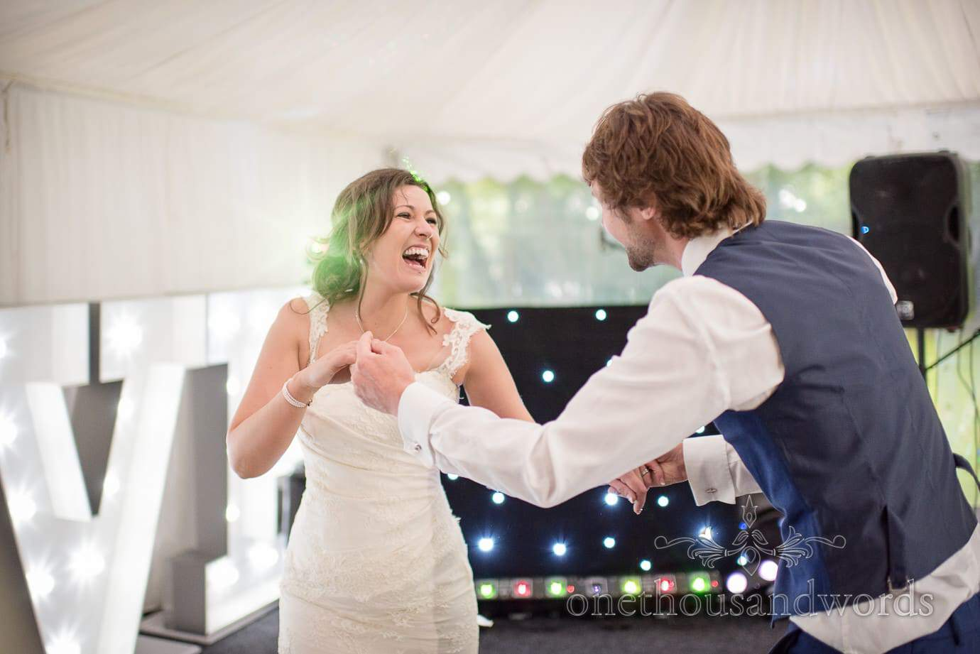 Laughing bride dances with wedding guest in marquee at The Old Vicarage Wedding