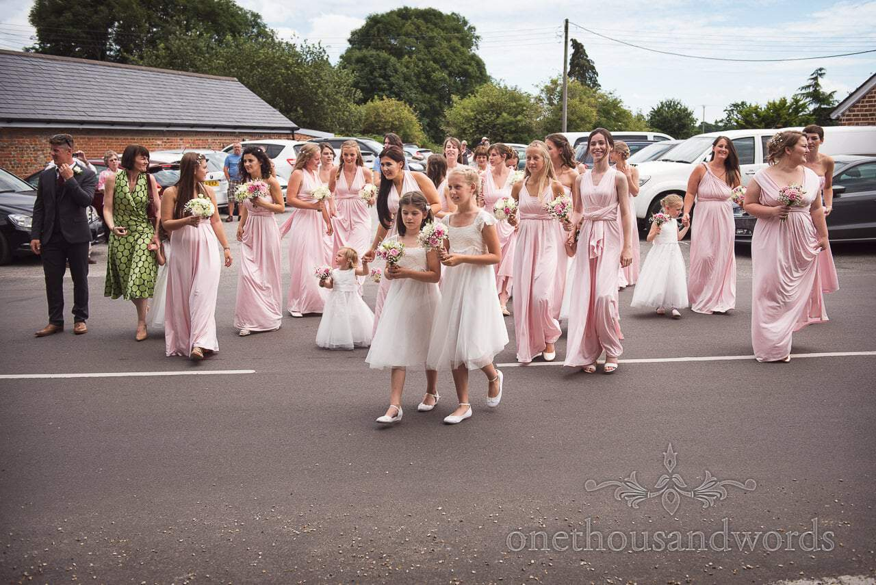 Lots of bridesmaids in pink bridesmaids dresses cross road with flower girls