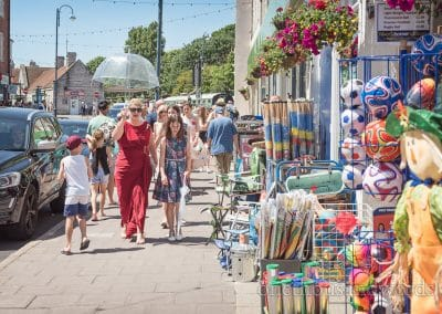 Maid of honour in red dress and wedding guests walk on crowded high street in Swanage