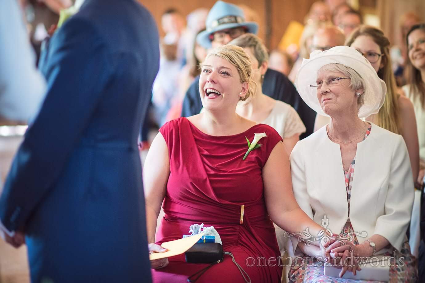 Maid of honour in red dress laughs during wedding ceremony at Purbeck House Hotel