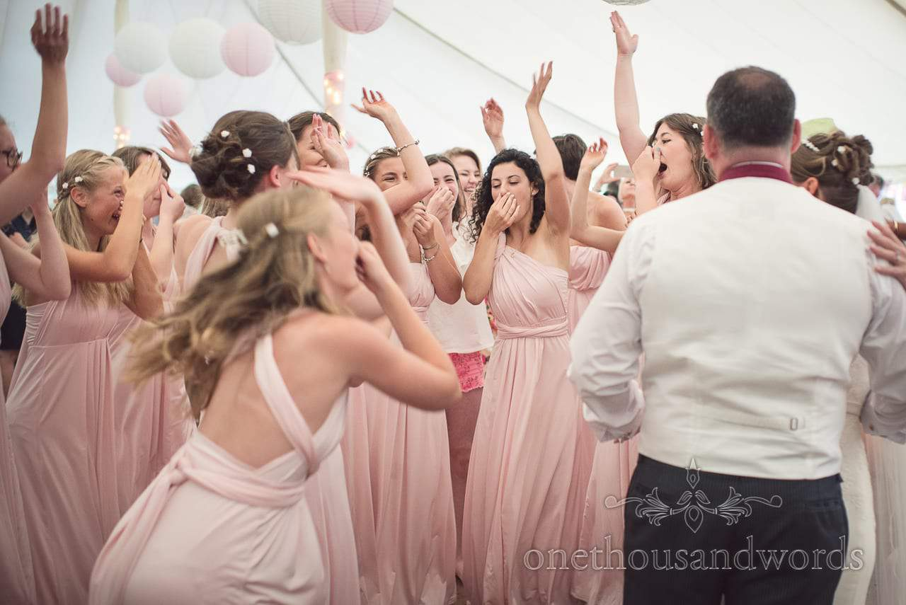 Mass of bridesmaids dancing in pink bridesmaids dresses in wedding marquee