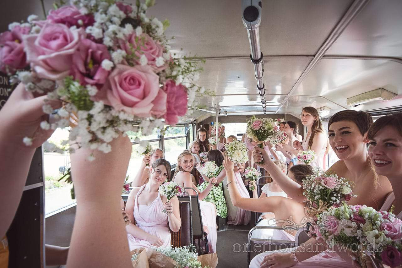 Mass of bridesmaids in pink bridesmaids dresses hold up wedding bouquets in bus