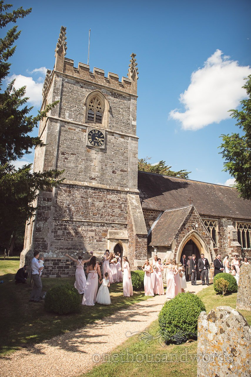 Mass of bridesmaids in pink bridesmaids dresses outside Dorset stone church wedding venue