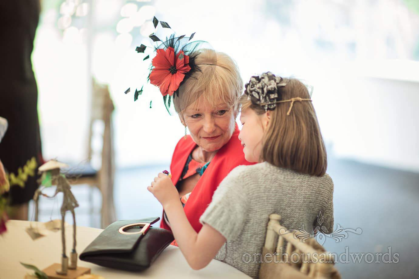 Mother of bride in red and black fascinator talks to child at The Old Vicarage Wedding