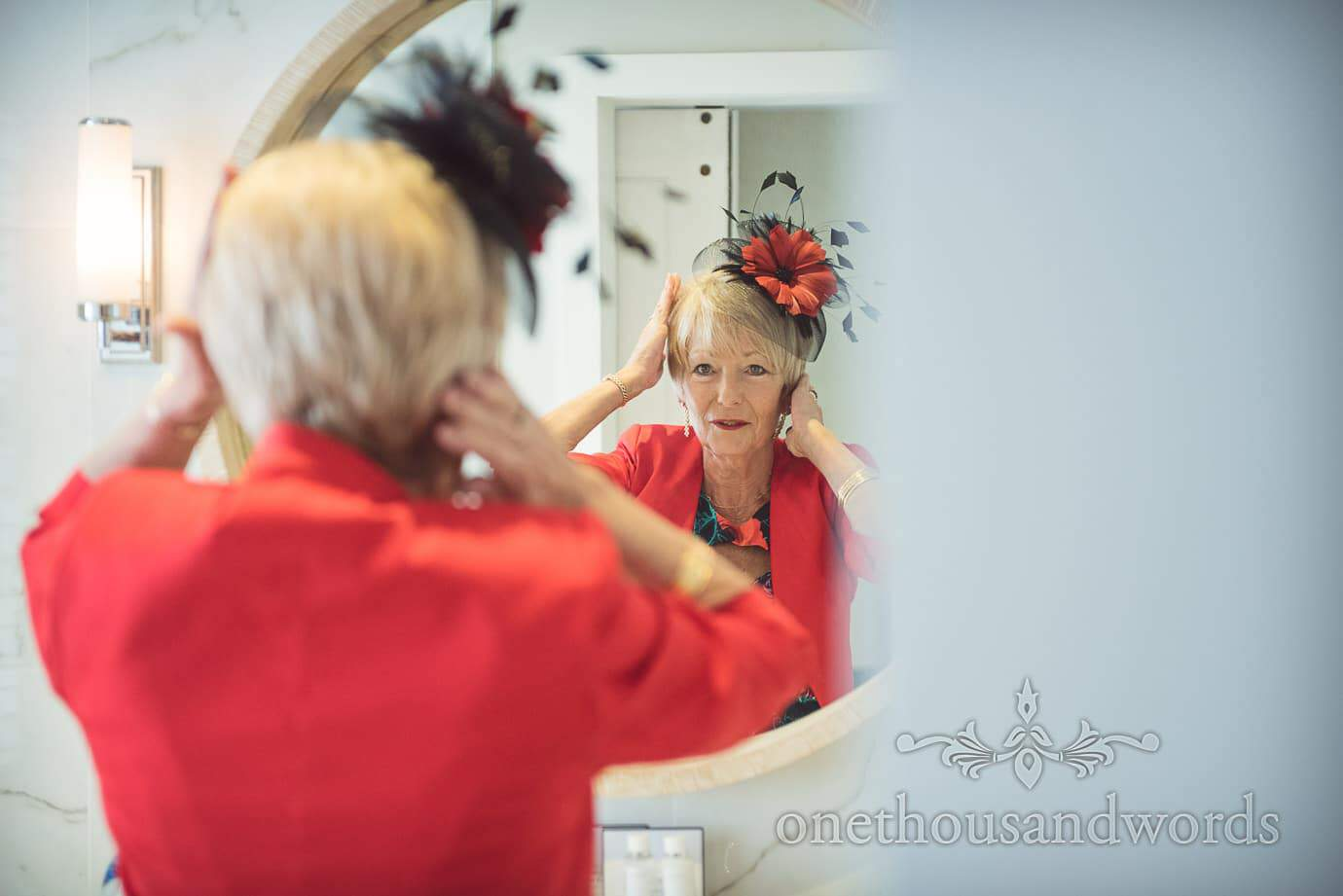 Mother of bride in red jacket and red flower and black feather wedding fascinator