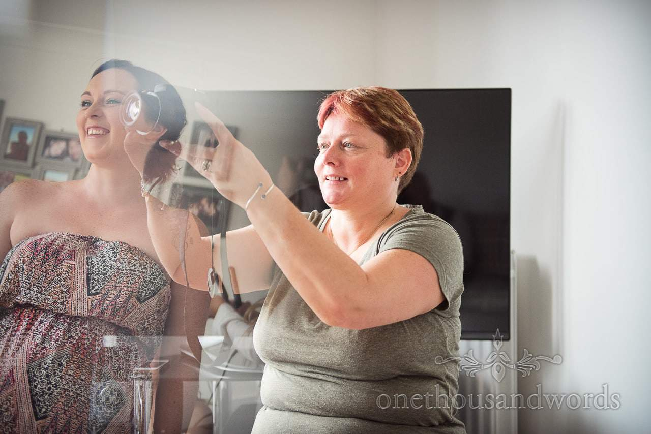 Mother of bride takes wedding preparation photograph as bridesmaid watches