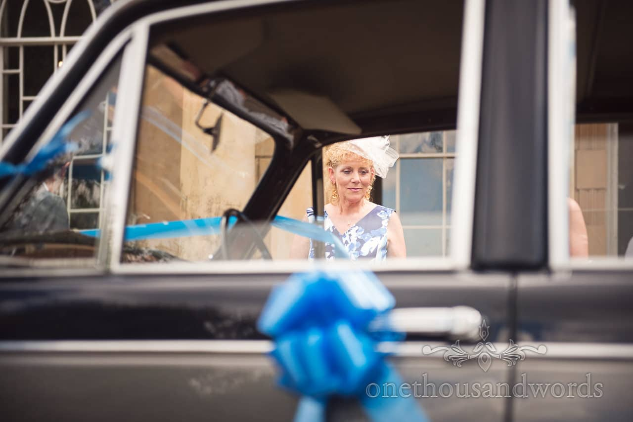 Mother of groom photographed through the window as she looks at classic Daimler wedding car