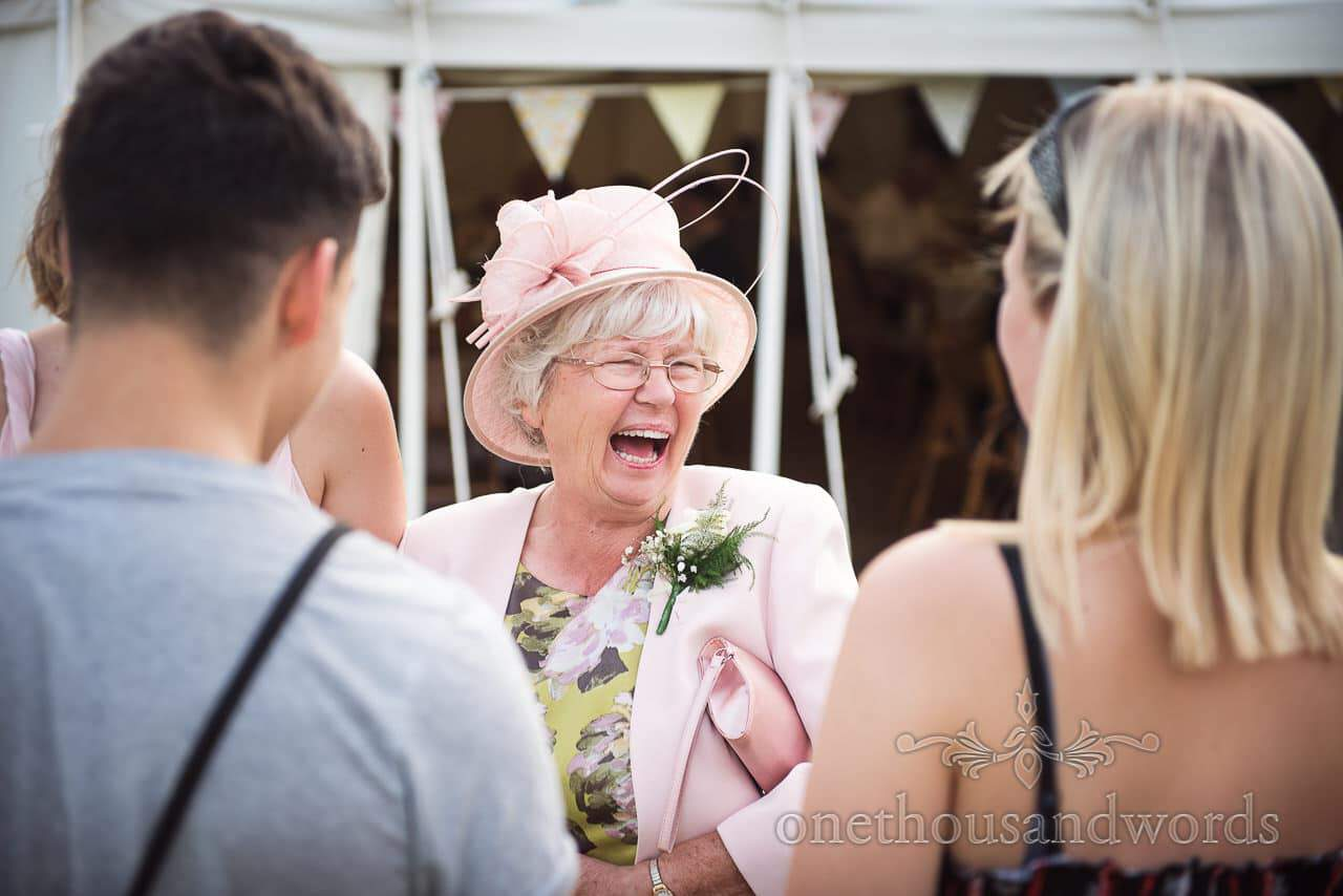 Mother of the bride in pink jacket and wedding hat laughs in front of marquee