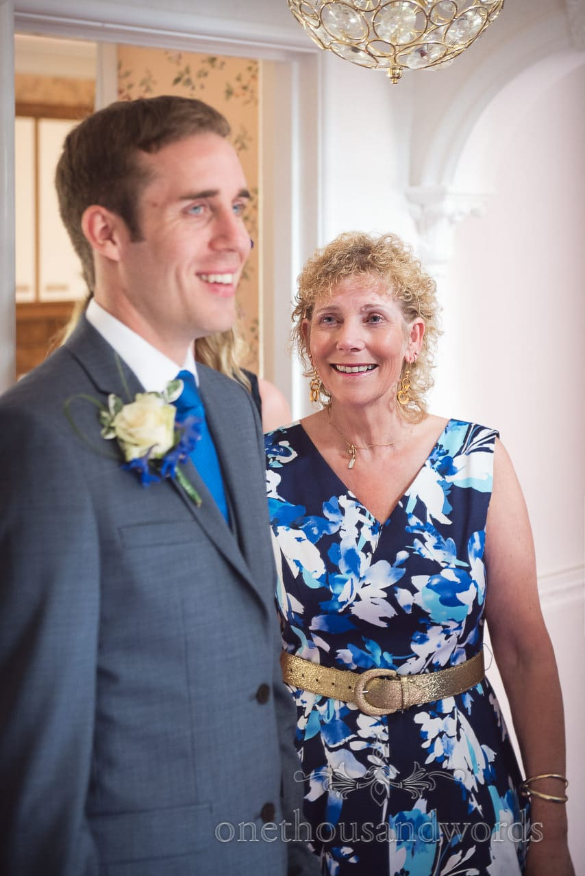 Mother of the groom in blue and white floral dress and gold belt laughs
