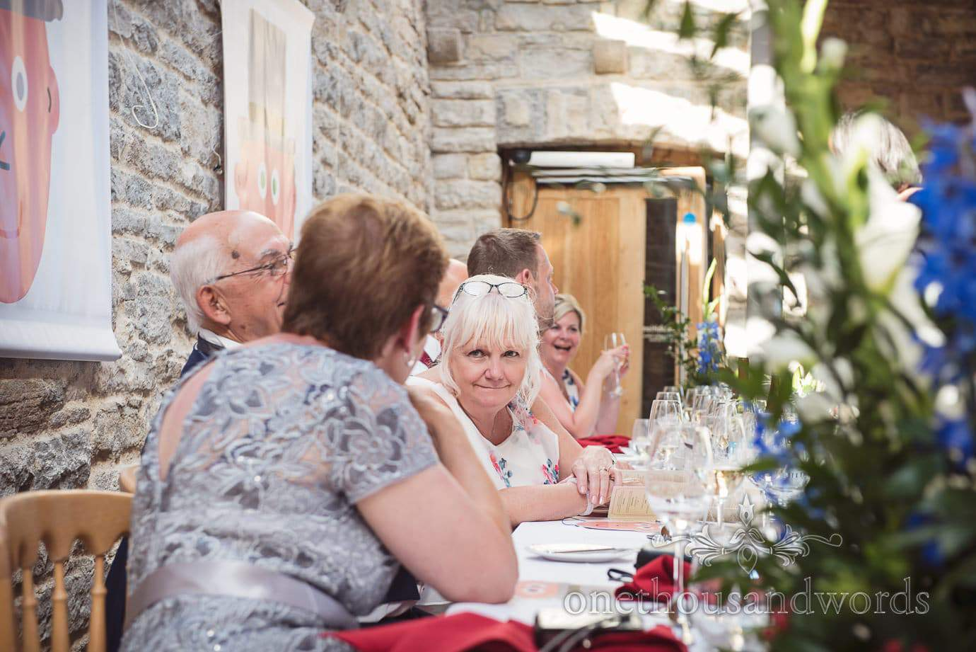 Mother of the groom in conversation on wedding top table at Durlston Castle