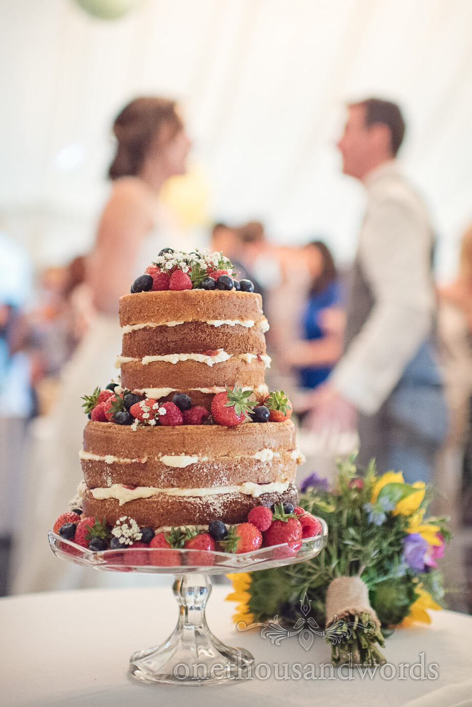 Naked Victoria sponge wedding cake with bride and groom at The Old Vicarage marquee