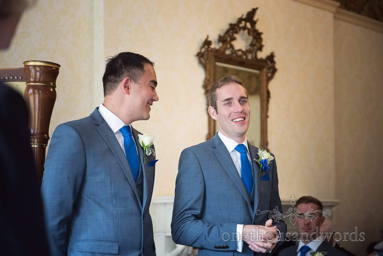 Nervous groom and best man in grey suits with blue ties and handkerchiefs laughing