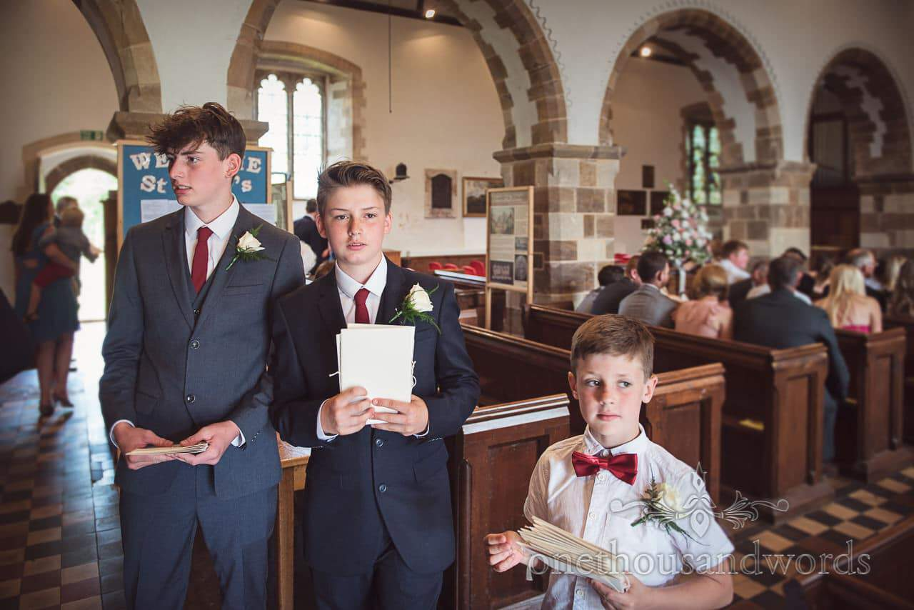 page boys hand out wedding programmes at English countryside church wedding