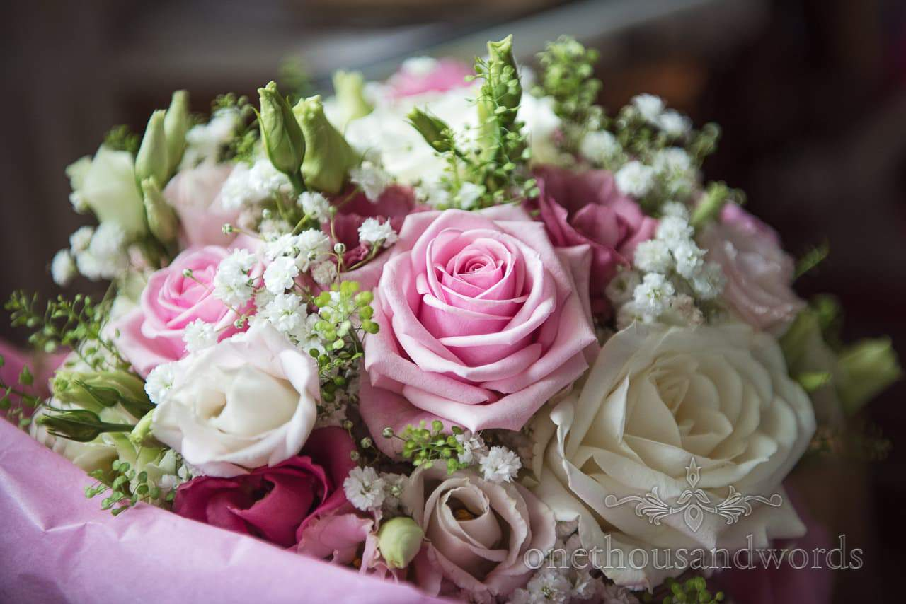 Pink and white rose wedding bouquet photograph with green foliage
