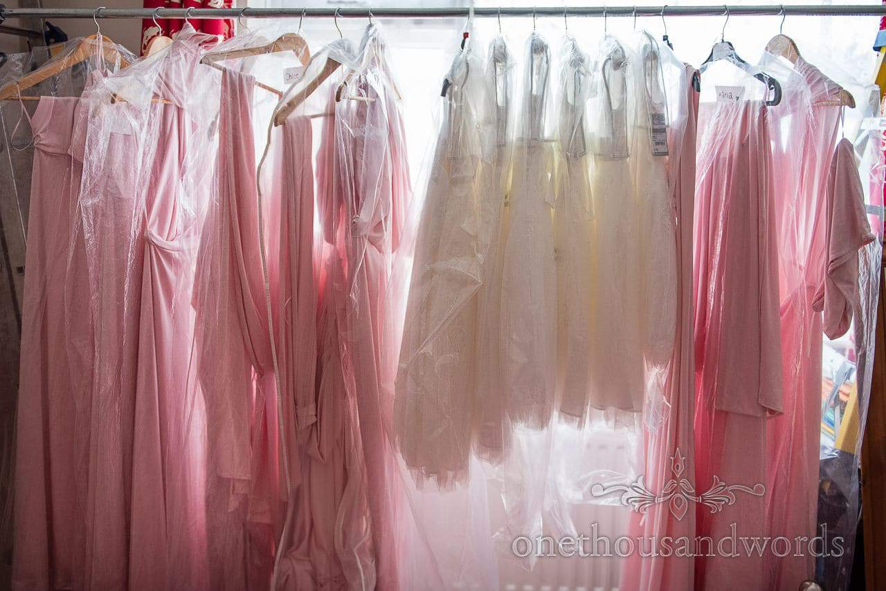 Pink bridesmaids dresses hanging on wedding morning with white flower girls dresses