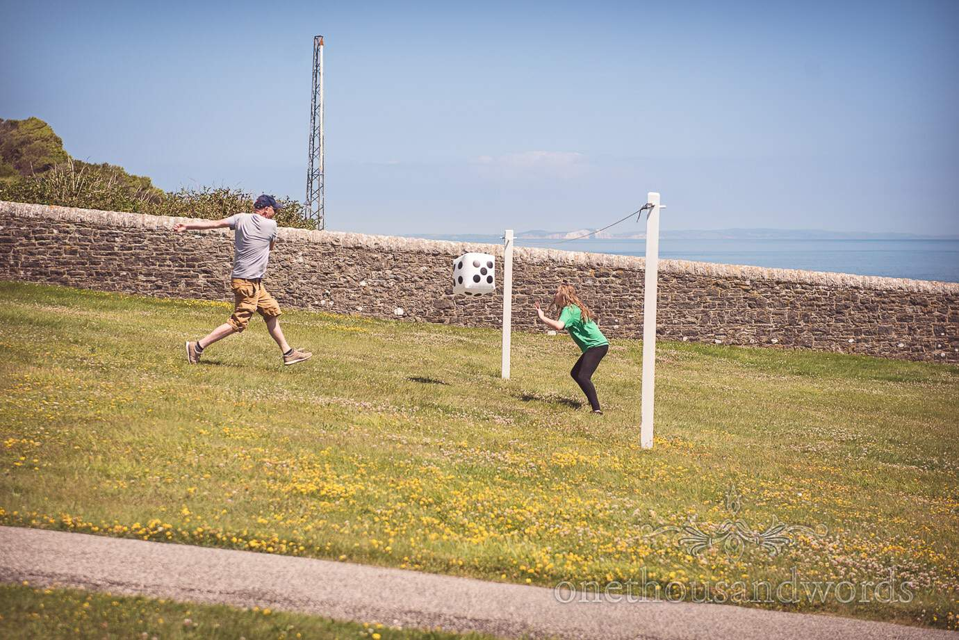 Playing football with giant inflatable dice with sea views at Durlston Lighthouse wedding