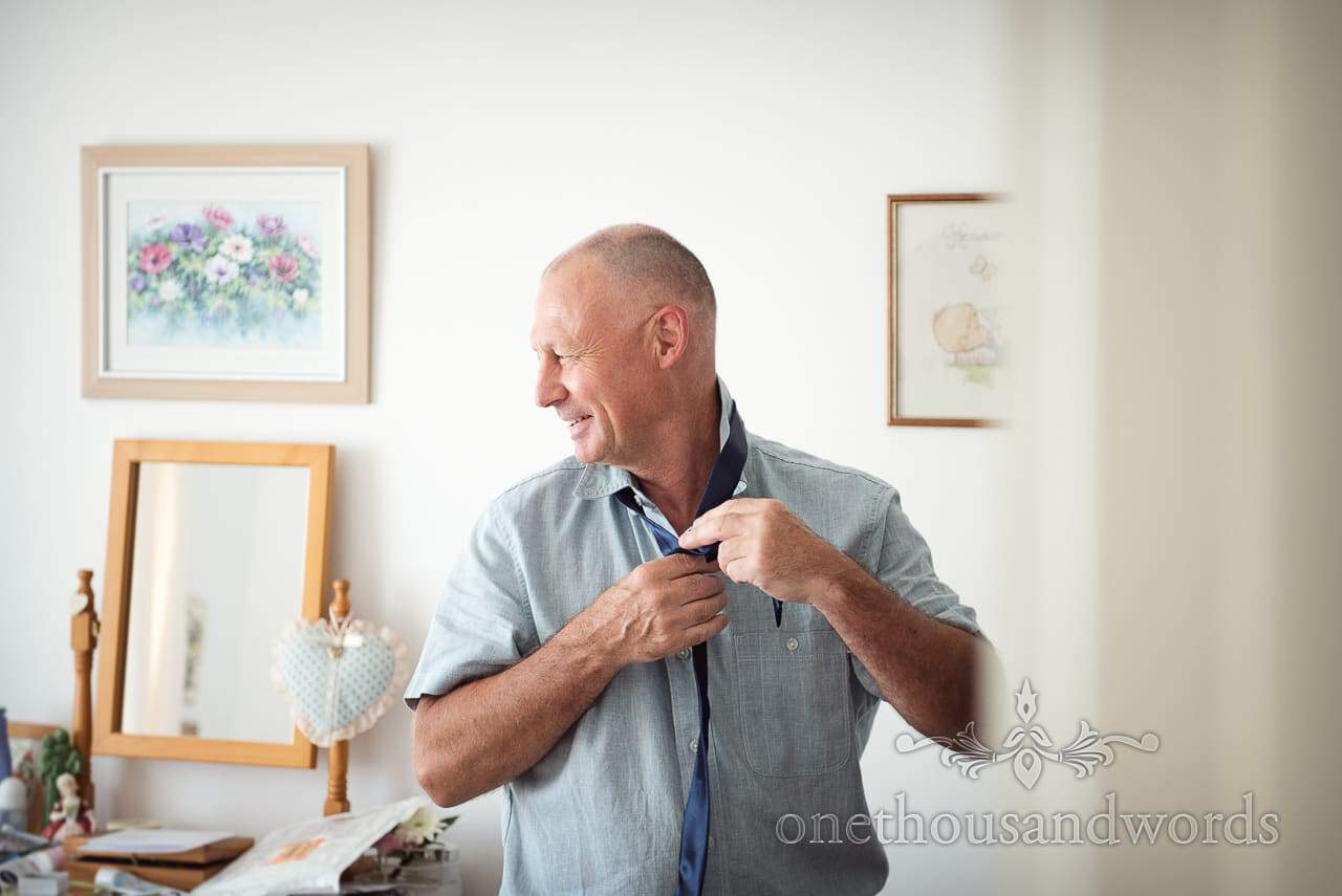 Portrait photograph of bride's brother tying blue tie on wedding morning preparations